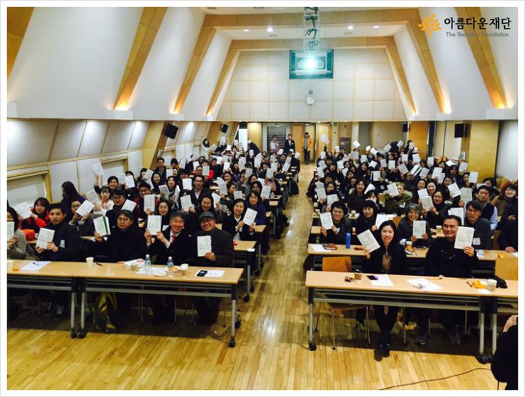 즐거운 모금, 행복한 기부' 강연 행사에 참여한 사람들 모두 책을 들고 사진을 찍음