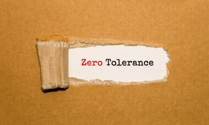 The text Zero Tolerance appearing behind torn brown paper